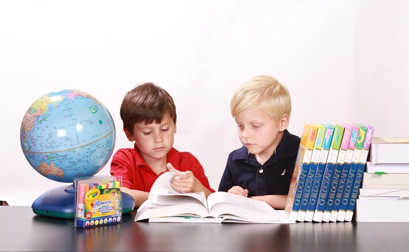 Two children sitting at a table with school supplies such as a globe, highlighters and books on it, reading a